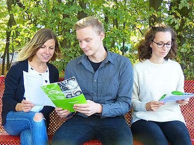 Drei Studenten sitzen auf der Bank und schauen HTW Broschüre an.